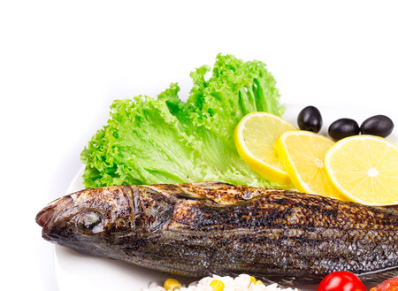 pikeperch: Grilled fish with vegetables. On a white plate as haute cuisine. Stock Photo