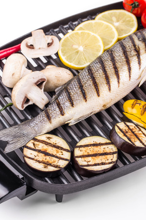 pikeperch: Grilled fish with vegetables On a black pan.
