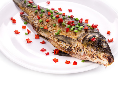 Fried fish with onion and pepper. Located on a white background. photo