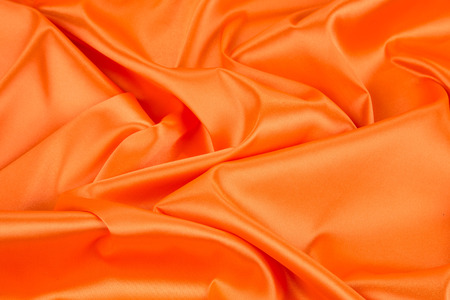 Orange silk drapery. Isolated as a whole background. Stock Photo