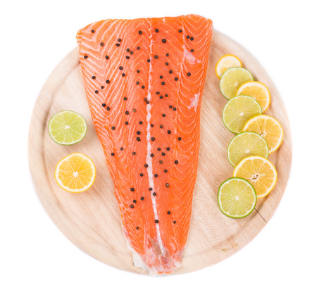 seafish: Raw salmon steak on cutting board. Isolated on a white background.