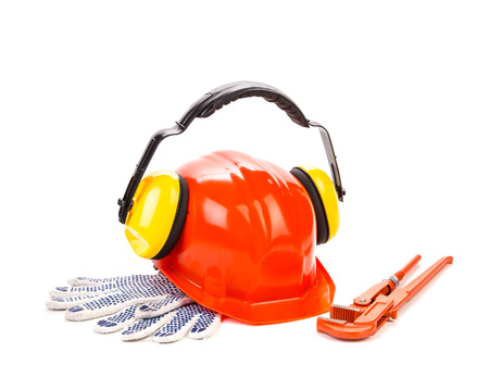 Red hard hat with working tools. Isolated on a white background. photo