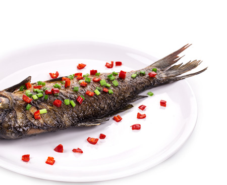fish isolated: Fried fish with red peppers and onion on a plate. Isolated in white background