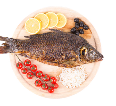 broil: Grilled carp fish with lemon and tomatoes. Isolated on a white background.