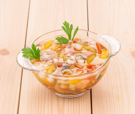 sued: Fresh homemade vegetable soup on wood. Whole background. Stock Photo