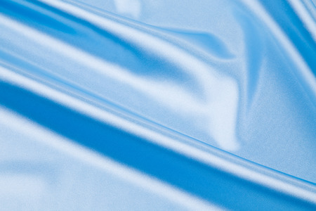 cloth texture: Soft folds of blue silk cloth texture. Whole background.