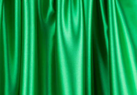 satiny cloth: Green silk drapery. Isolated as a whole background.