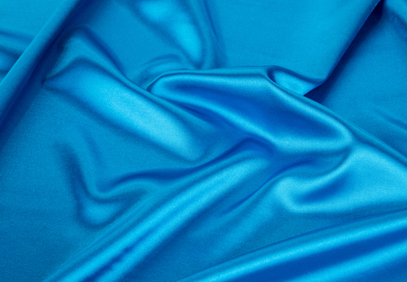 blue silk: Blue silk soft folds of cloth. Whole background. Stock Photo