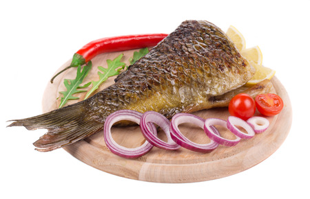 fish plate: Close up of grilled carp steak. Isolated on a white background.