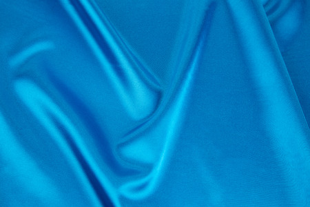 blue silk: Folds of blue silk cloth texture. Whole background.
