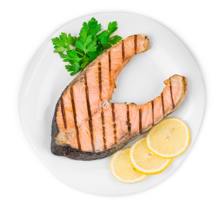 fish plate: Grilled salmon steak with vegetables on plate. Isolated on a white background.