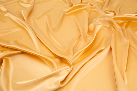 sexual abstract: Golden silk drapery. Isolated as a whole background.