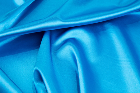 blue silk: Folds of light blue silk cloth texture. Whole background.