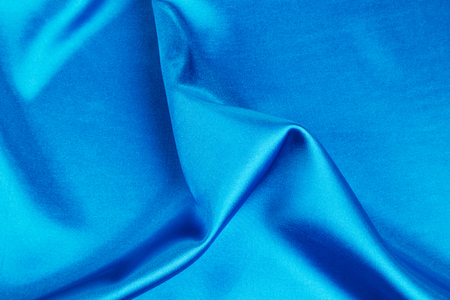 blue silk: Cloth with folds of deep blue silk texture. Whole background.