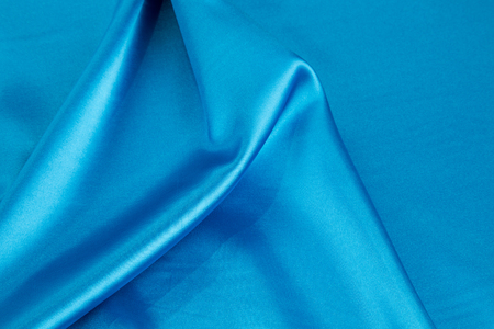 blue silk: Some soft folds of light blue silk cloth. Whole background.