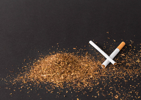 Heap of tobacco and cigarettes. Located on a black background.