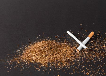 Hoop van tabak en sigaretten. Gelegen op een zwarte achtergrond.