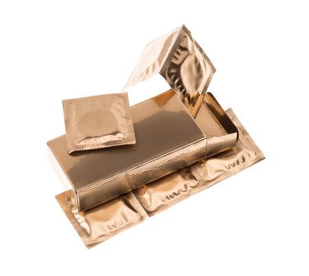 condones: Condones en caja de oro aisladas sobre fondo blanco
