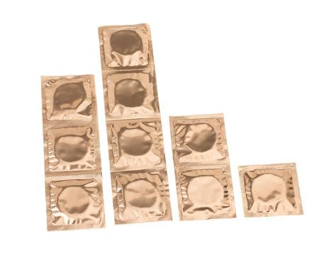 condones: Conjunto de condones en el embalaje de oro aisladas sobre fondo blanco