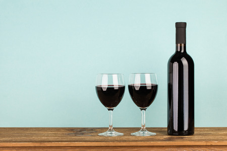 wine bottle: Bottle with red wine and glasses on wooden table