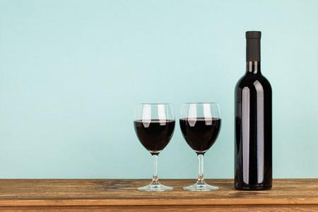 bouteille de vin: Bouteille de vin et des verres rouge sur la table en bois