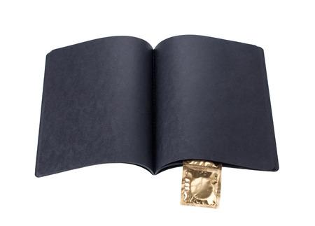 condones: cuaderno de cart�n negro con los condones de oro sobre un fondo blanco Foto de archivo