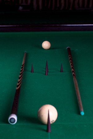 pool cues: Billiard balls and cues in a pool table in the closeup Stock Photo