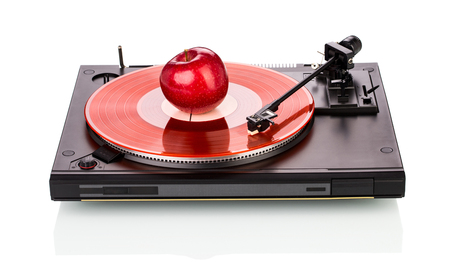 record player: old fashioned turntable playing a track from black vinyl with an apple. Stock Photo