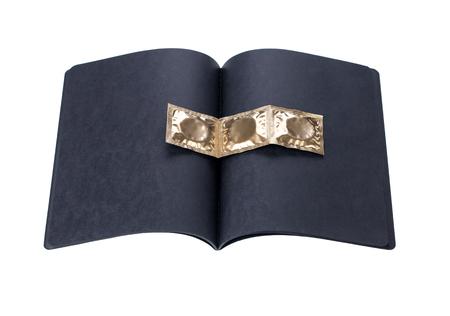 condones: cuaderno de cartón negro con los condones de oro sobre un fondo blanco Foto de archivo