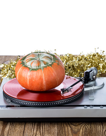 Analog music player with christmas decoration and pumpkin on a wooden table
