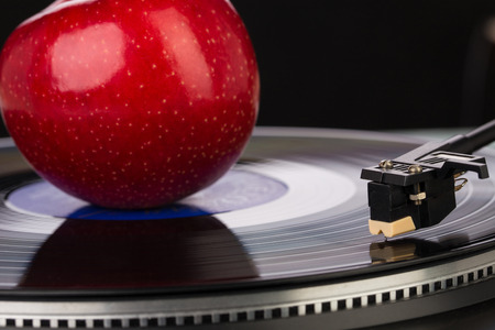 sixties: old fashioned turntable playing a track from black vinyl with an apple. Stock Photo