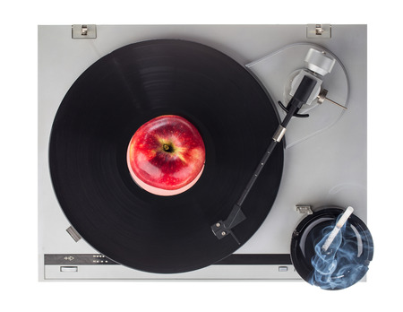 astray: old fashioned turntable playing a track from black vinyl with an apple astray and cigarettes.