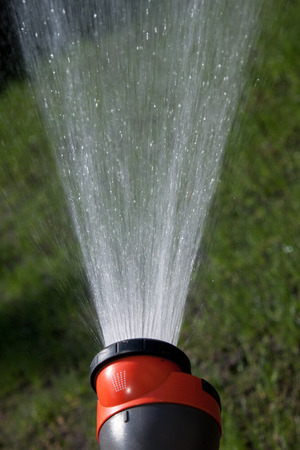 Water flying out of the hose. Vertical image.