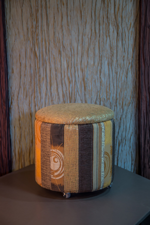 pouffe: Contemporary striped beige fabric pouffe on a background of decorative wall