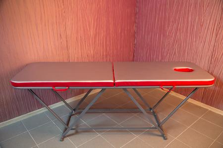 masajes relajacion: cama de relajación rojo para el masaje de pie en la esquina de un cuarto con papeles pintados texturizados