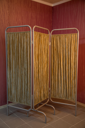 folding screens: Folding screen standing in the corner of a room with red wallpapers