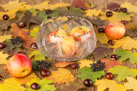 crystal bowl: Apples in a crystal bowl on wooden table with autumn leaves and chestnuts Stock Photo