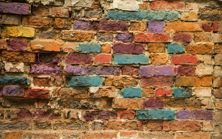 bricks background: Colourful brick wall painted in blue, yellow, red by street artists