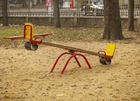 Kids geschommel op zandige speelplaats in de herfst stadspark. Achtergrond: omheining, auto, bomen