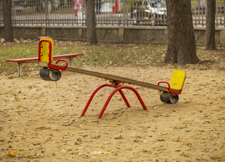 seesaw: Kids seesaw on sandy playground in autumn city park. Background: fence, car, trees