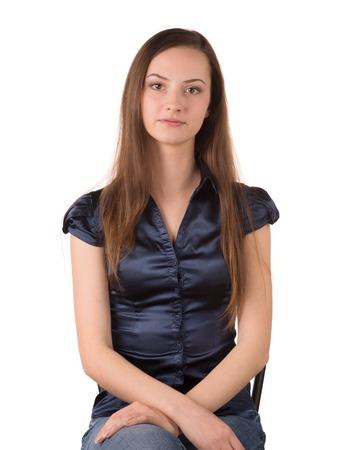 ojos marrones: Retrato de la hermosa mujer joven sentada en una silla y que presenta, fondo blanco