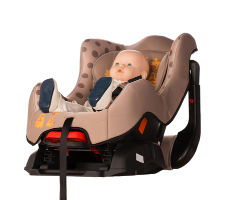 booster: Baby doll fastened in a booster seat for car on white background Stock Photo