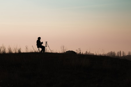 hilltop: Silhouette of Nature photographer on a hilltop against the sky