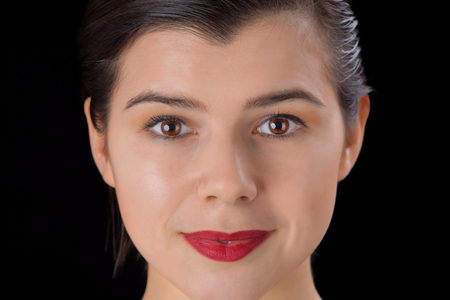 hazel eyes: Beautiful face of a smiling pretty woman with big red lips and hazel eyes and clean skin isolated on black background