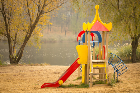 climbing frames: A beautiful view on kids slides and climbing frames on a sandy playground by the lake in an autumn park