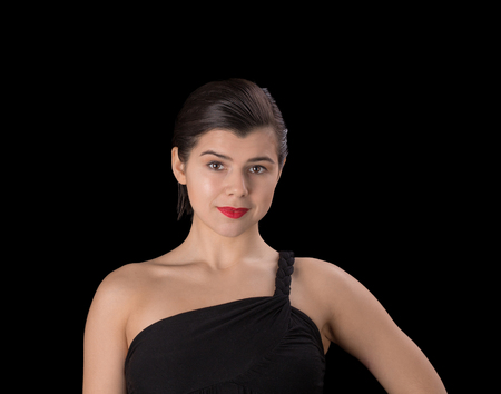 short haircut: Beautiful brunette woman in black dress with a short haircut and a bare shoulder isolated on black background