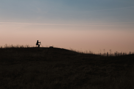 hilltop: Silhouette of nature photographer taking shots on a hilltop against the sky Stock Photo