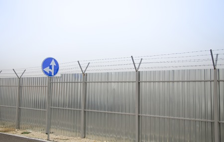 perimeter: A closeup of straight and left turn arrow sign at the perimeter with barbed wire and construction fence around airport Stock Photo