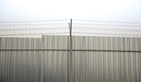 perimeter: A closeup of perimeter fencing with barbed wire and construction fence against the sky Stock Photo