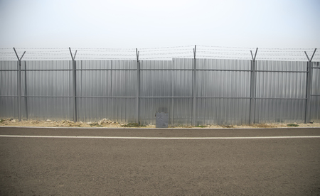 perimeter: Perimeter fencing with barbed wire and construction fence along the road to stop trespassing